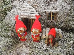 Christmas card - gnomes in front of their cosy home in the forest - stock photo