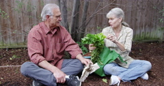 Mature couple sitting and talking in garden Stock Footage