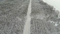 lonely car on snow-covered road and wood. Aerial shot Stock Footage