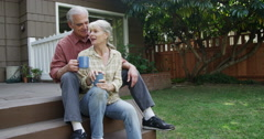 Senior couple having coffee petting dog in their yard Stock Footage