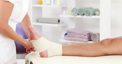 Physiotherapist wrapping injured ankle in bandage Stock Footage