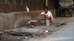 Indian man washing dishes by a street drain-away in Mumbai. Stock Footage