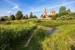 Traditional russian landscape with small tranquil river and old abandoned chu - stock photo