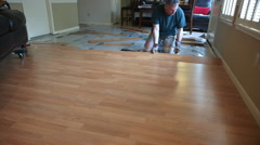 Wide shot of workman removing laminate flooring Stock Footage