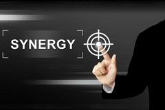 Business hand pushing synergy button on touch screen Stock Photos