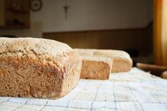 Homemade wholewheat loaf of bread close up on kitchen cloth as Christianity symb - stock photo