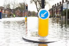 Flooded Urban Road With Traffic Lights - stock photo