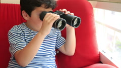 Child looking through binoculars Stock Footage