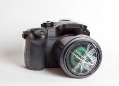 Digital reflex camera with the front lens broken. Stock Photos