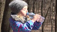 Little girl drinks water from a bottle. 4K UltraHD, UHD Stock Footage