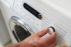 Close Up Of Man Choosing Cycle Program On Washing Machine Stock Photos