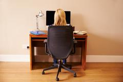 Woman Sitting At Desk Working At Computer In Home Office Stock Photos