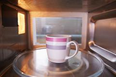 Warming Cup Of Coffee Inside Microwave Oven - stock photo