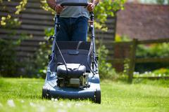 Close Up Of Man Working In Garden Cutting Grass With Mower - stock photo