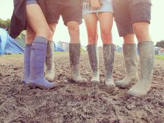 Close Up Of Friends In Wellington Boots Walking To Festival Stock Photos