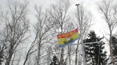 New Brunswick Canadian Provincial Flag being lowered from half staff Stock Footage