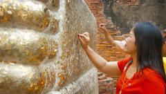 AYUTTHAYA, THAILAND - CIRCA FEB 2015: Worshippers Pressing coin on Gold Leaf Stock Footage