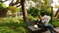 Stock Video Footage of Workman with newspaper on the bench in park