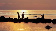 Silhouettes of a group of teenager netting fish in the sea - stock footage