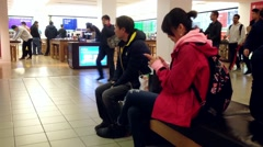People reading moblie message at rest area beside Microsoft store Stock Footage