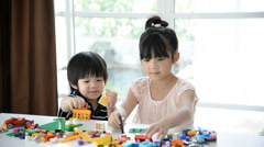 Little asian children playing with colorful construction blocks Stock Footage