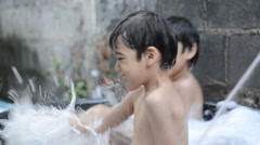 Little sibling boy playing in baht outside together Stock Footage