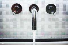 Faucet in Bathroom with Running Water Stock Photos