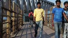 Indian men crossing a bridge in Mumbai. Stock Footage