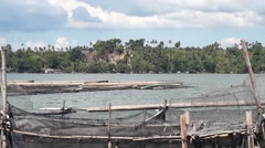 Mountain lake floating fish cages tracking shot Stock Footage