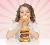 Happy little girl eating junk food Stock Photos