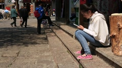 Young woman sitting and using smart phone at shuhe old town in Lijiang Stock Footage