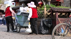 Senior women in uniform cleaning the street of Lijiang old town Stock Footage