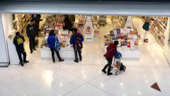 Bookstore in airport. Passengers walking, looking the books Stock Footage