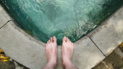 Person standing at pool with focus on feet Stock Footage