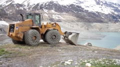 Backhoe in front of a empty dam - JIB SHOT Stock Footage