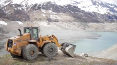 Backhoe in front of a empty dam - JIB SHOT - Up'n down Stock Footage