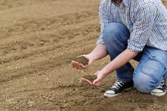Farmer Checking Soil Quality of Fertile Agricultural Farm Land Kuvituskuvat