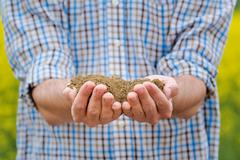 Farmer Checking Soil Quality of Fertile Agricultural Farm Land - stock photo