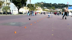 Roller skaters performing tricks on the Nice Boulevard Stock Footage