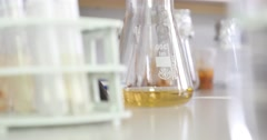 A person in a laboratory taking samples from an Erlenmeyer flask Stock Footage