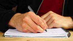 Man Sits Down at Desk & Writes in Notebook HD Stock Footage