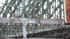 Barbwire fence with bridge in background 4k - stock footage