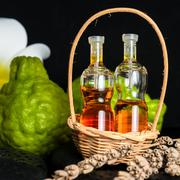 Aromatic spa concept of bottles essential oil in basket, flower and bergamot Stock Photos