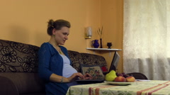 Happy pregnant woman work with laptop and write with pencil Stock Footage