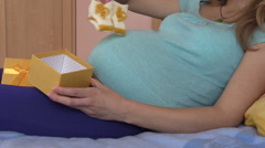 Pregnant girl woman open gift box with handmade baby shoes Stock Footage