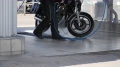 Biker washing the motorcycle with  water pressure from the hose Stock Footage