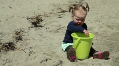 Little girl playing with sand on beach with a dog, close up Stock Footage
