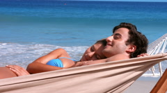 Happy couple relaxing in hammock on beach Stock Footage
