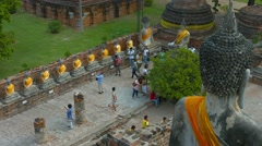 AYUTTHAYA, THAILAND - CIRCA FEB 2015: Tourists Viewing Row of Identical Buddh Stock Footage