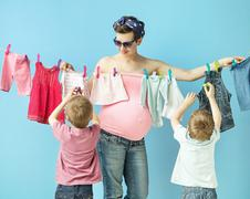 Mom doiing the laundry with her sons - stock photo